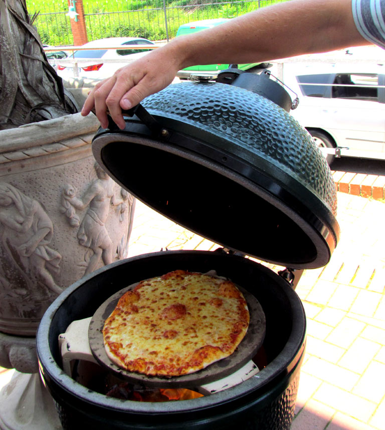 A Remo's pizza cooking on the Big Green Egg